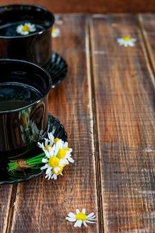 Duas xícaras de chá preto com camomila no fundo da mesa de madeira.