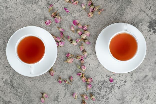 Duas xícaras de chá preto com flores secas em mármore.