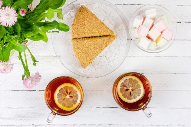 Duas xícaras de chá preto com limão, pedaços de bolo, marshmallows e uma flor rosa