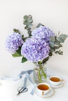 Duas xícaras de chá preto em uma bela xícara de porcelana branca com um corte dourado. lindo buquê de hortênsia roxa em cima da mesa. conceito de cerimônia do chá.