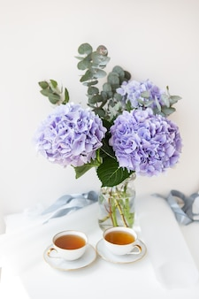Duas xícaras de chá preto em uma bela xícara de porcelana branca com um corte dourado. lindo buquê de hortênsia roxa em cima da mesa. pausa para o chá.