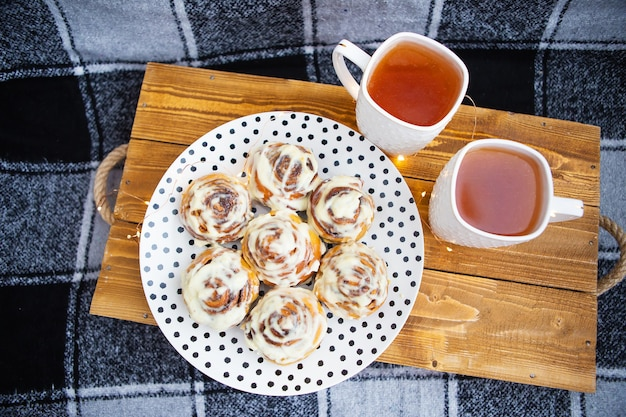 Duas xícaras de chá preto ficam em uma bandeja de madeira no sofá com uma manta quadriculada preta e branca. close-up de rolos de canela fresca e perfumada mentira em um prato com bolinhas. a guirlanda está piscando