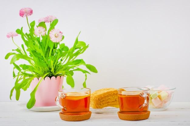 Duas xícaras de chá preto, marshmallows, fatias de bolo e um vaso de flores rosa em cima da mesa