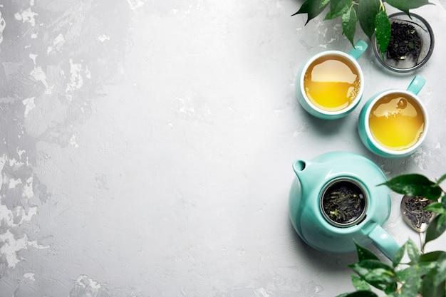 Duas xícaras de chá verde com um bule de chá em uma mesa de concreto cinza