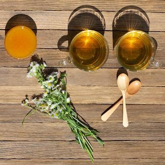 Duas xícaras de chá verde, mel, um buquê de camomila e colheres de pau na mesa
