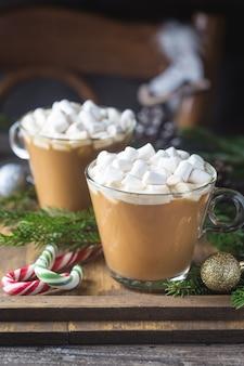 Duas xícaras de chocolate cacau com marshmallow em uma madeira com enfeites de natal
