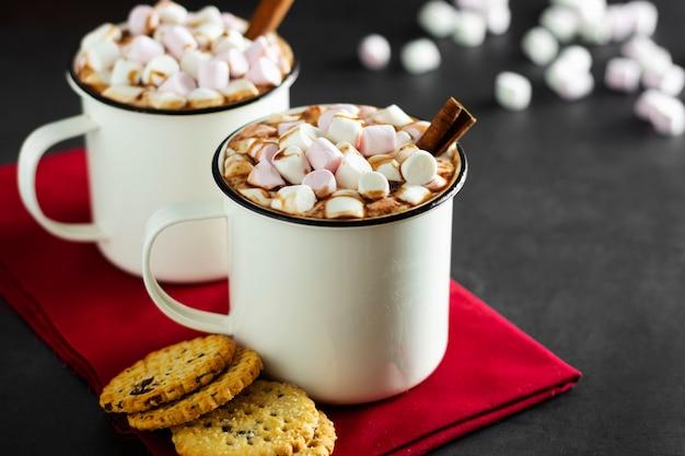 Duas xícaras de chocolate quente, cacau ou bebida quente com marshmallows e biscoitos doces no escuro