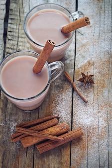 Duas xícaras de chocolate quente com canela em um fundo de madeira.