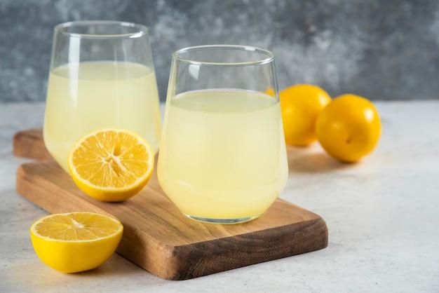 Duas xícaras de limonada saborosa em uma placa de madeira.