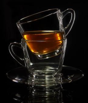 Duas xícaras de pé um no outro com chá em um fundo preto com reflexão