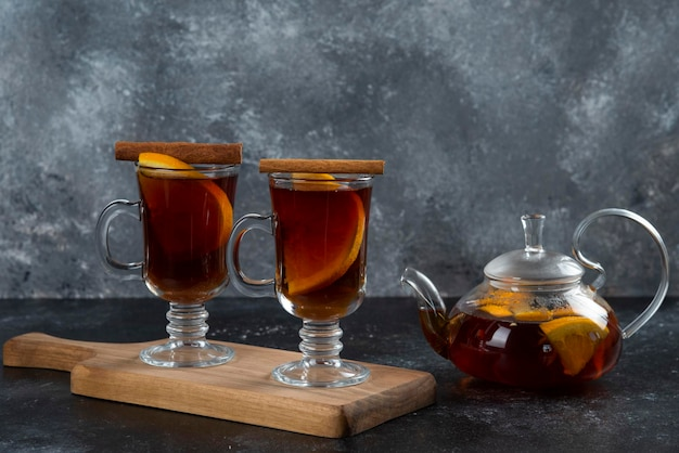 Duas xícaras de vidro com um delicioso chá e paus de canela.