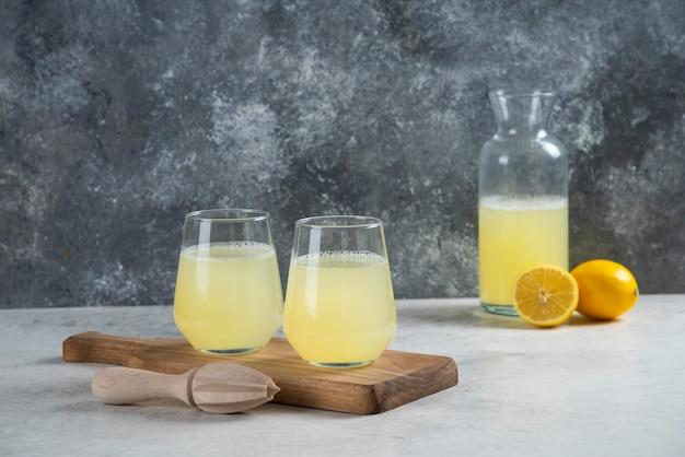Duas xícaras de vidro de limonada em uma placa de madeira.