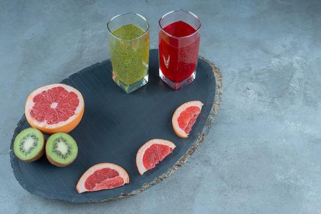 Duas xícaras de vidro de sucos naturais com fatias de frutas diversas.