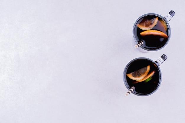 Duas xícaras de vinho tinto na superfície cinza