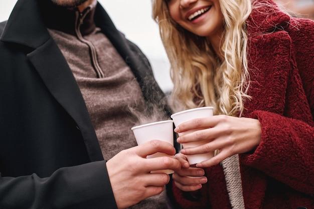 Duas xícaras juntas. jovem casal está bebendo uma bebida quente em frente ao balcão de um café moderno