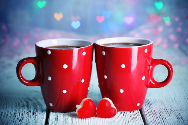 Duas xícaras vermelhas na mesa com luzes de fundo