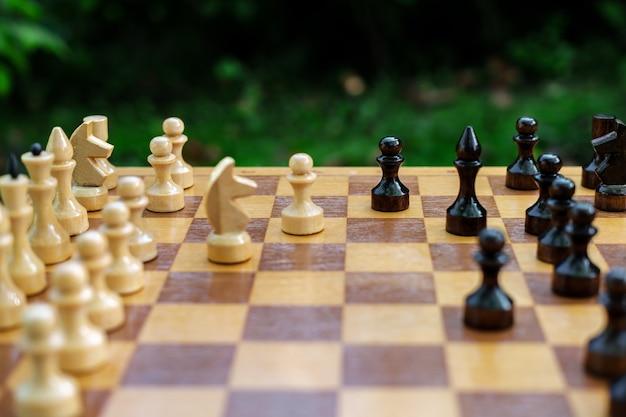 Duelo de xadrez no jardim com o arranjo de peças pretas e brancas sobre um tabuleiro de madeira.