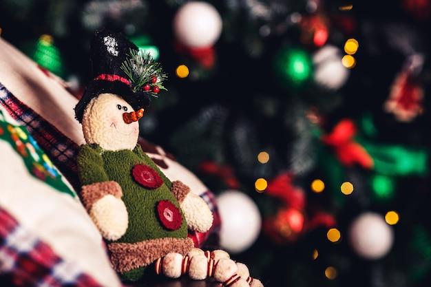 Duende de brinquedo de natal sentado na mala na superfície da árvore de natal.