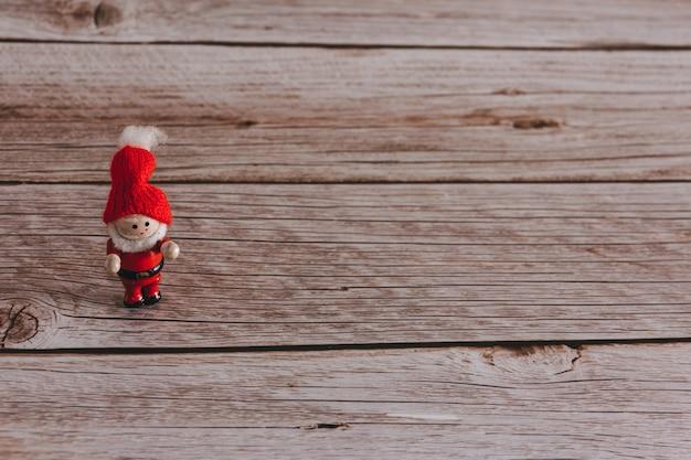 Duende decorativo de natal em fundo de madeira. copie o espaço. foco seletivo.