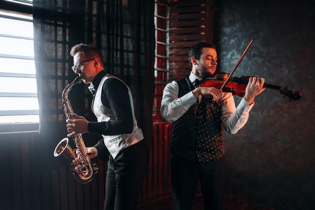 Dueto de saxofonista e violinista tocando melodia clássica