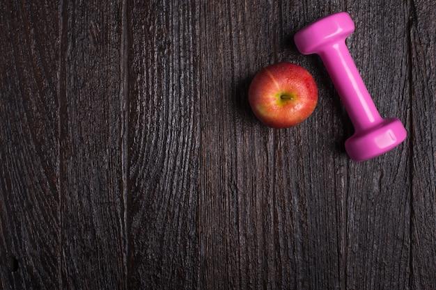 Dumbbell e maçã em fundo de madeira escura. vestuário físico e equipamento. moda esportiva, acessórios esportivos, equipamento esportivo. para um conceito saudável