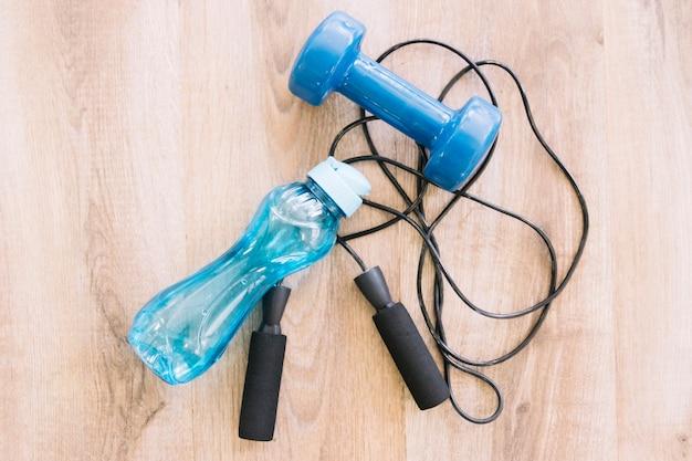 Dumbell, corda salteada e garrafa de água