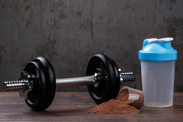 Dumbell e proteína em pó