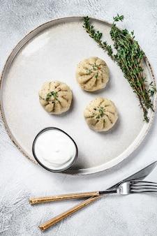 Dumplings cozinhados asiáticos manti com carne picada em um prato.