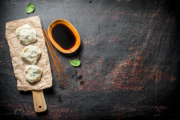 Dumplings manta em uma tábua com molho de soja na mesa rústica escura.