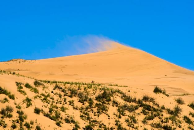 Duna contra o fundo de um céu azul brilhante o vento sopra a areia do cume da duna paisagem da natureza selvagem papel de parede da área de trabalho