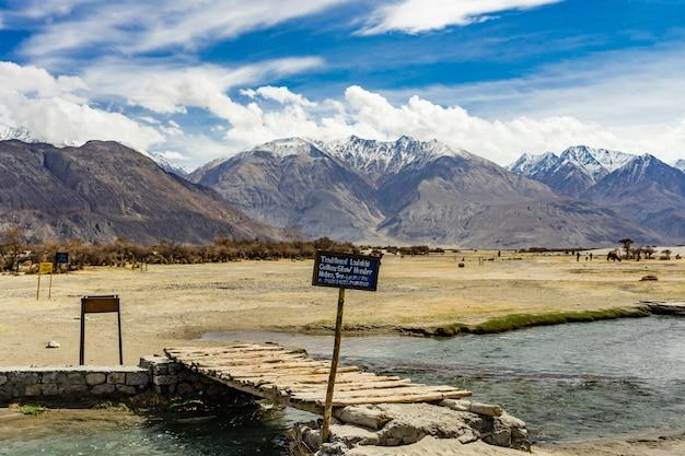 Duna de areia de sobremesa com céu azul nublado, nubra vale em leh ladakh, norte da índia