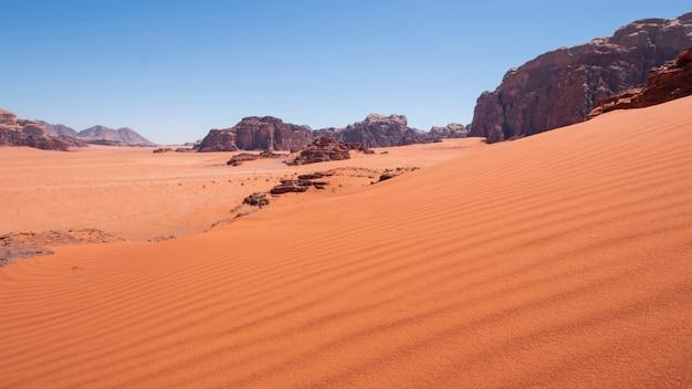 Duna de areia no fundo das falésias no deserto de wadi rum na jordânia. paisagem de areia quente.