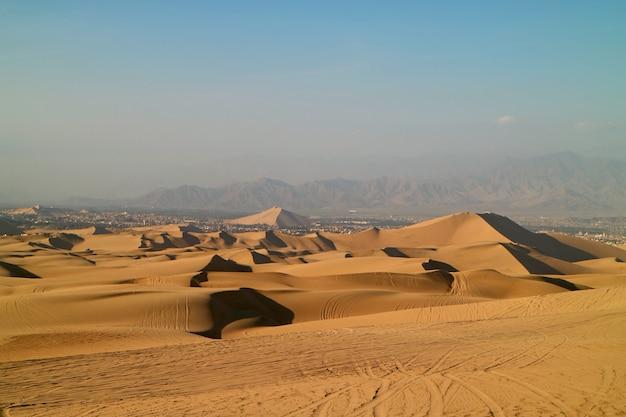 Dunas de areia dourada com a roda imprime de buggies, huacachina, ica, peru