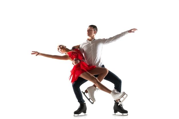Duo de patinação artística isolado na parede branca com copyspace. dois desportistas praticando e treinando em ação e movimento.
