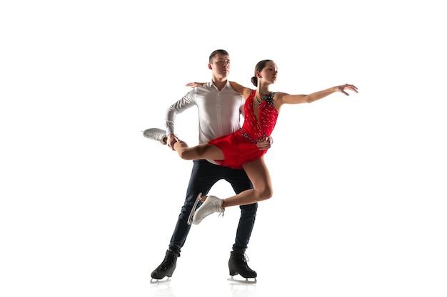 Duo de patinação artística isolado na parede branca do estúdio com copyspace. dois desportistas praticando e treinando em ação e movimento. cheio de graça e sem peso. conceito de movimento, esporte, beleza.