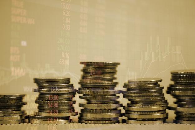 Dupla exposição da pilha de moedas com tela do mercado de ações e vara de vela