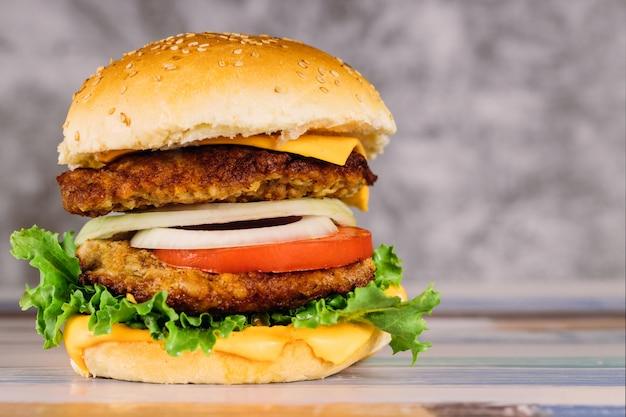 Duplo hambúrguer suculento com legumes na mesa.