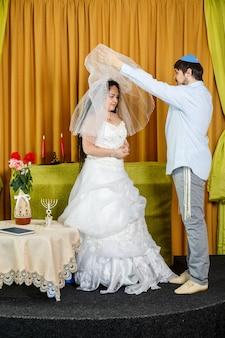 Durante a cerimônia da chupá em um casamento na sinagoga, o noivo levanta o véu do rosto da noiva. foto vertical