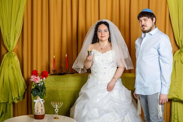 Durante a cerimônia de chupá na sinagoga, a noiva segura uma taça de vinho na mão, o noivo fica por perto