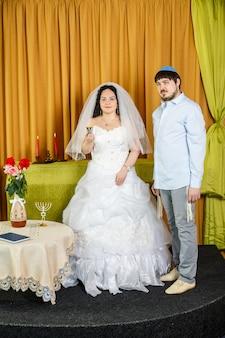 Durante a cerimônia de chupá na sinagoga, a noiva segura uma taça de vinho para kidush em sua mão, o noivo fica por perto