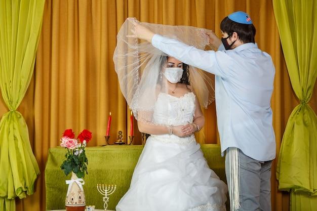 Durante a cerimônia de chupá na sinagoga, o noivo mascarado levanta o véu do rosto da noiva