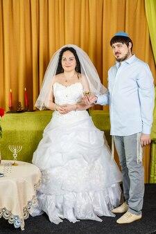 Durante a cerimônia de chupa na sinagoga, o noivo segura uma taça de vinho para kidush em sua mão, a noiva está por perto