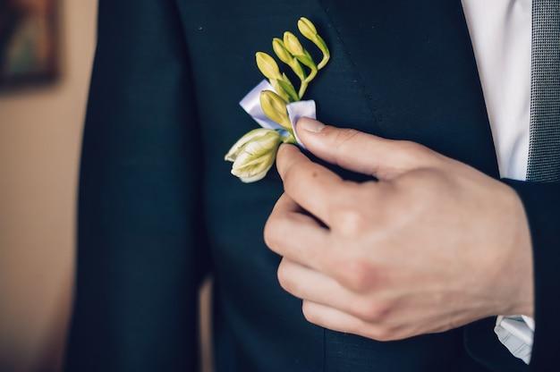 Durante a sessão de fotos do casamento, o noivo endireita a flor na lapela com a mão. conceito de casamento.