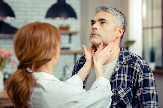 Durante o exame médico. bom homem maduro com a cabeça erguida em frente ao médico