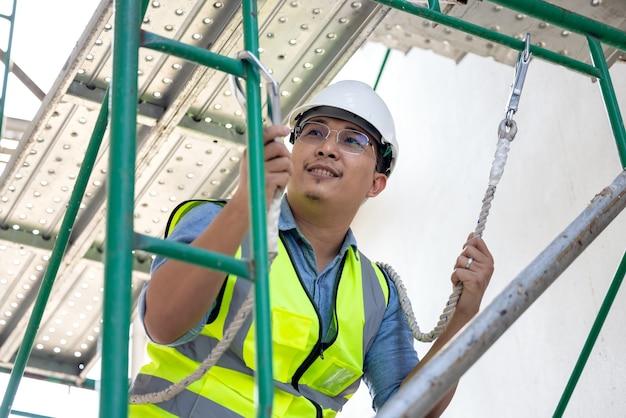 Durante o trabalho em altura, um operário da construção usa um cinto de segurança. em um fundo de uma plataforma de perfuração para uma plataforma estrutural