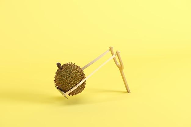 Durian inteiro em um estilingue em fundo amarelo