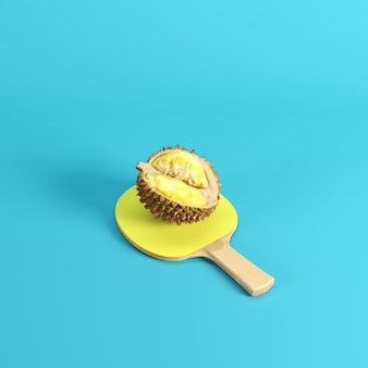Durian maduro descascado, rei dos frutos, na pá do pong do pong com a borracha amarela isolada no fundo azul