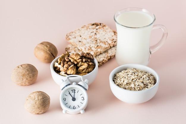 Durma bem. alimentos para uma boa noite de sono - leite, nozes, pão crocante, aveia e despertador em fundo rosa