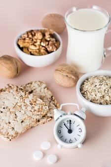 Durma bem. alimentos para uma boa noite de sono - leite, nozes, pão crocante, aveia, remédio para dormir e despertador em fundo rosa. visão vertical
