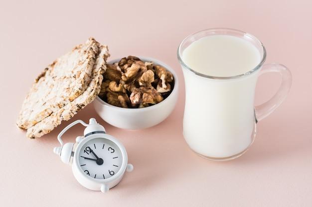 Durma bem. alimentos para uma boa noite de sono - leite, nozes, pão crocante e despertador em fundo rosa